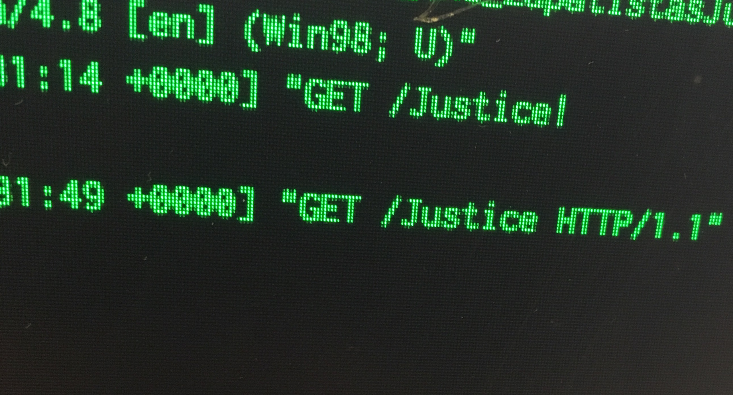 photograph of green text on computer screen reading: 'GET /Justice HTTP/1.1'.